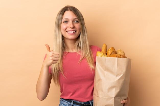 Giovane donna bionda che tiene una borsa piena di pane isolato sulla parete beige che dà un pollice in alto gesto
