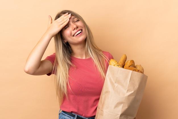 Giovane donna bionda che tiene un sacchetto pieno di pane isolato sulla risata beige della parete