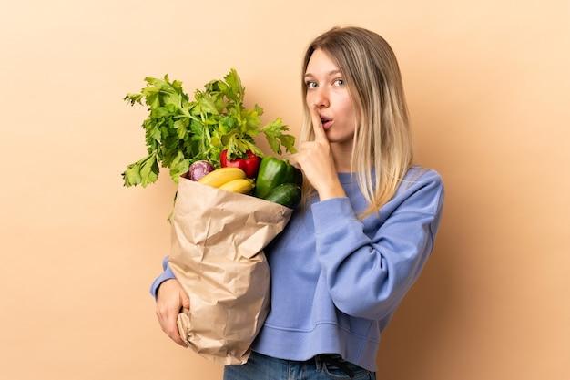 Giovane donna bionda che tiene un sacchetto pieno di verdure sopra isolato facendo gesto di silenzio
