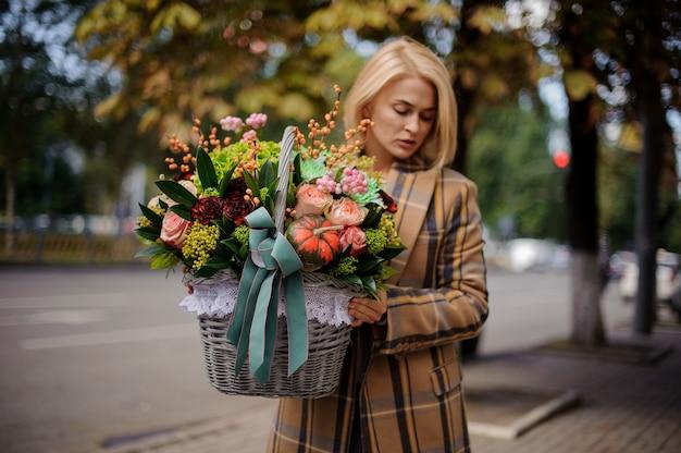 Giovane donna bionda che tiene un grande cestino di vimini di fiori contro la città