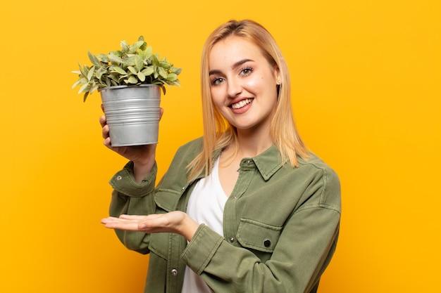 Giovane donna bionda che tiene un oggetto con entrambe le mani sullo spazio della copia laterale, mostrando, offrendo o pubblicizzando un oggetto