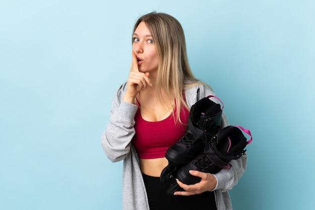 Giovane donna bionda che tiene un pattini a rotelle isolati sul colore rosa che fa gesto di silenzio