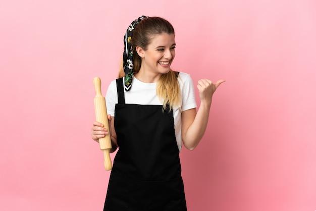 Giovane donna bionda che tiene un mattarello isolato sulla parete rosa che punta di lato per presentare un prodotto