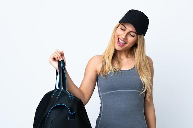 Giovane donna bionda che tiene una borsa di sport sopra la parete bianca isolata che celebra una vittoria