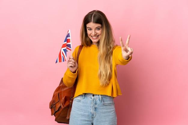 Giovane donna bionda che tiene una bandiera del regno unito isolato sorridente
