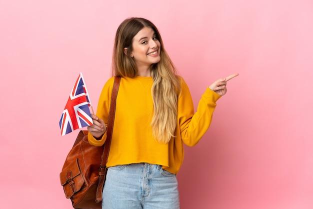 Giovane donna bionda in possesso di una bandiera del regno unito isolato su uno spazio bianco che punta il dito a lato