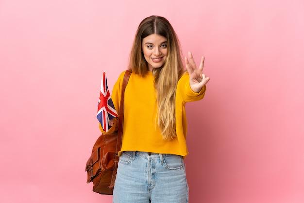 Giovane donna bionda che tiene una bandiera del regno unito isolata sul muro bianco felice e contando tre con le dita