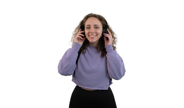 La giovane donna bionda sta ascoltando la musica con le cuffie senza fili isolate