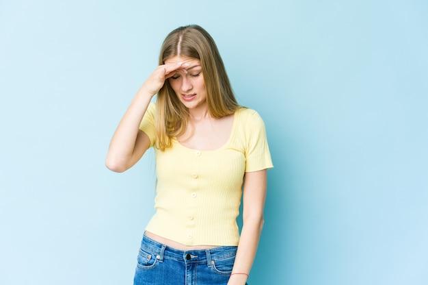 Giovane donna bionda isolata sulla parete blu con mal di testa, toccando la parte anteriore del viso.