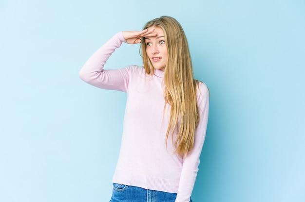 Giovane donna bionda isolata sulla parete blu che guarda lontano tenendo la mano sulla fronte.