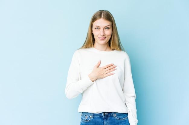 Giovane donna bionda isolata sulla parete blu che presta giuramento, mettendo la mano sul petto