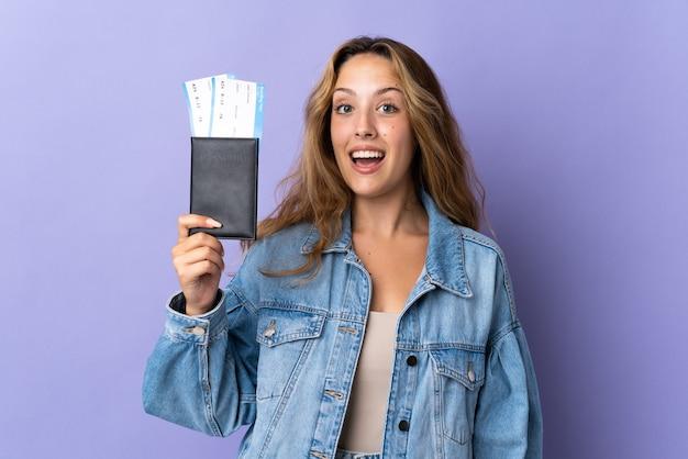 Giovane donna bionda isolata felice in vacanza con i biglietti aerei del passaporto