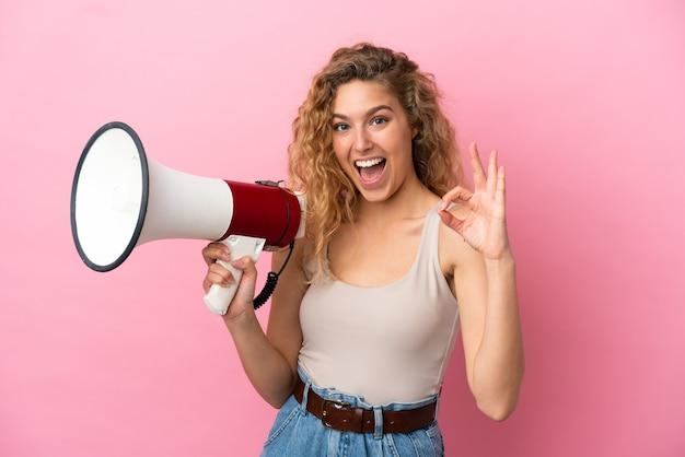 Giovane donna bionda isolata su sfondo rosa in possesso di un megafono e mostrando segno ok con le dita