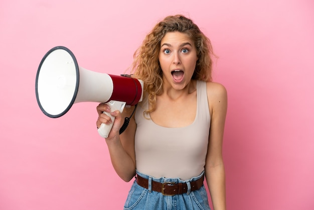 Giovane donna bionda isolata su sfondo rosa in possesso di un megafono e con espressione di sorpresa