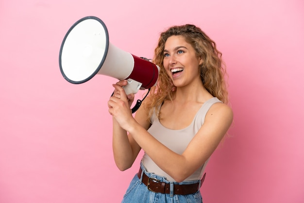 Giovane donna bionda isolata su sfondo rosa che grida attraverso un megafono per annunciare qualcosa