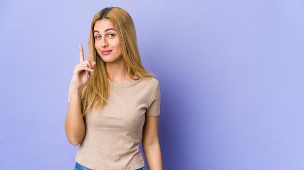Giovane donna bionda isolata sulla viola che mostra il numero uno con il dito.