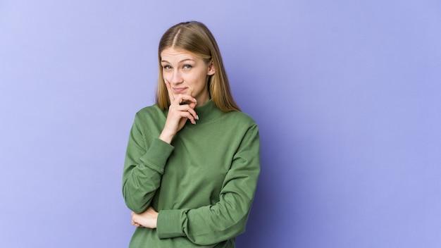 Giovane donna bionda isolata sul muro viola contemplando, pianificando una strategia, pensando al modo di fare impresa.