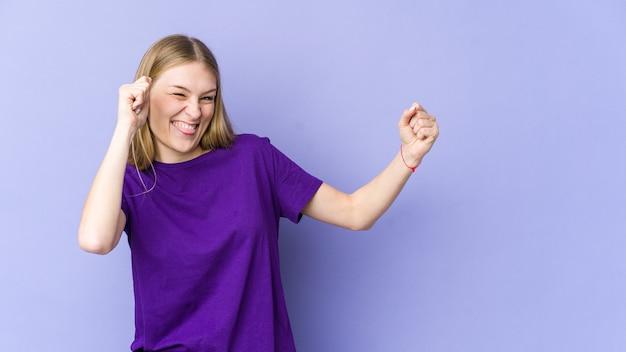 Giovane donna bionda isolata sulla parete viola ballando e divertendosi