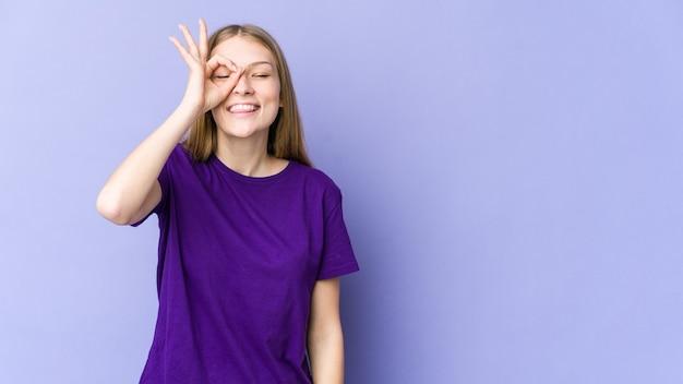 Giovane donna bionda isolata sulla parete viola eccitata mantenendo il gesto giusto sull'occhio.