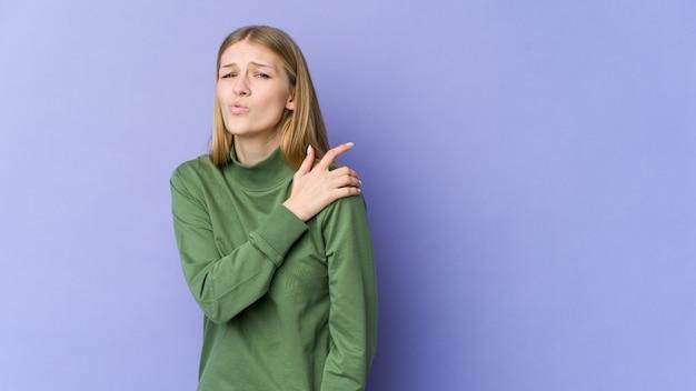 Giovane donna bionda isolata sulla parete viola che ha un dolore alla spalla