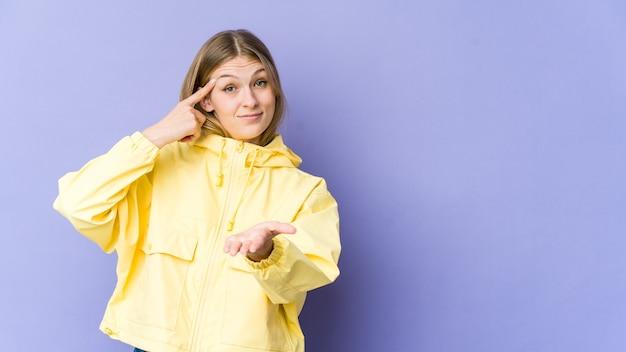 Giovane donna bionda isolata sulla parete viola che tiene e che mostra un prodotto a portata di mano.
