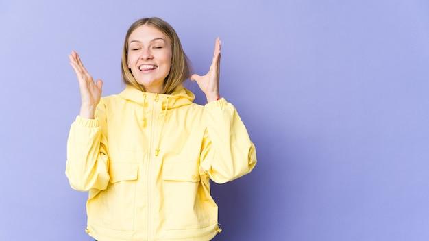 Giovane donna bionda isolata sul muro viola ride ad alta voce tenendo la mano sul petto