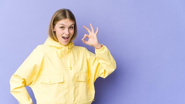 La giovane donna bionda isolata sulla parete viola strizza l'occhio e tiene un gesto giusto con la mano