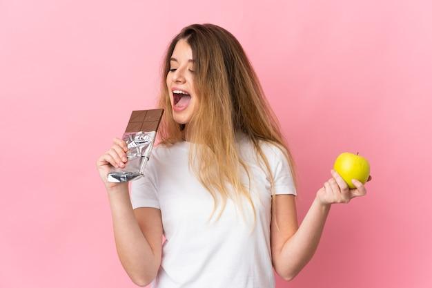 Giovane donna bionda isolata prendendo una tavoletta di cioccolato in una mano e una mela nell'altra