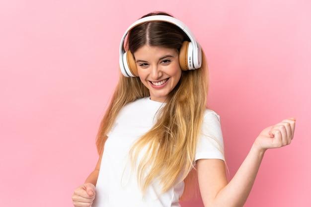 Giovane donna bionda sopra la parete isolata che ascolta musica e che fa il gesto della chitarra