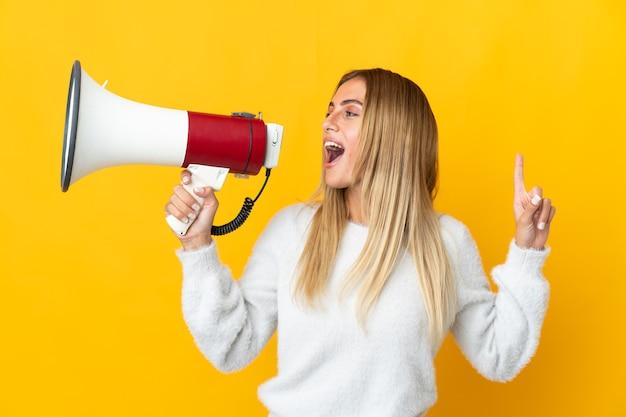 Giovane donna bionda sopra la parete isolata che grida tramite un megafono per annunciare qualcosa in posizione laterale