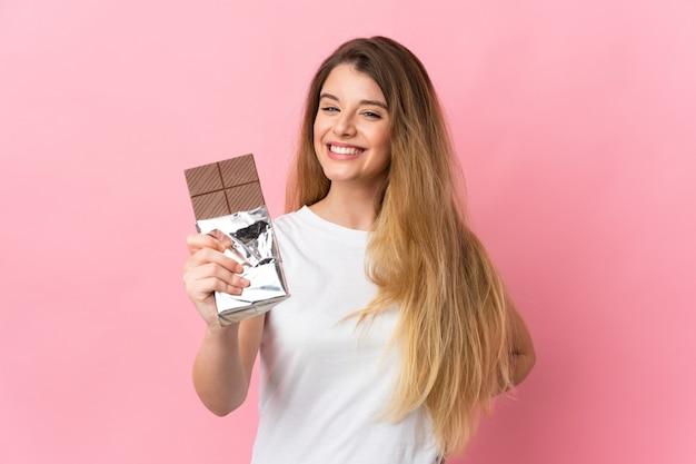 Giovane donna bionda sopra la parete isolata che prende una compressa di cioccolato e felice