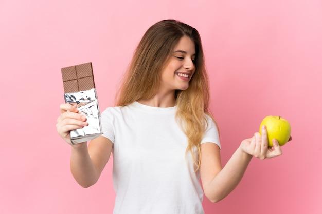 Giovane donna bionda sopra la parete isolata che prende una compressa di cioccolato in una mano e una mela nell'altra