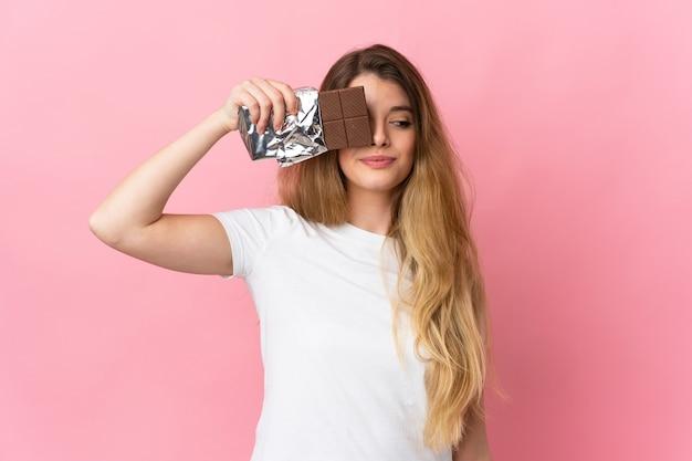 Giovane donna bionda sopra la parete isolata che prende una compressa di cioccolato e sorpresa