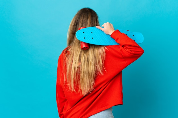 Giovane donna bionda sul muro isolato con un pattino in posizione posteriore