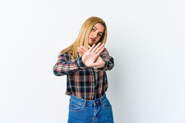 Giovane donna bionda isolata su bianco facendo un gesto di diniego
