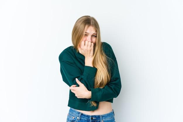 Giovane donna bionda isolata sulle unghie mordaci della parete bianca, nervosa e molto ansiosa.