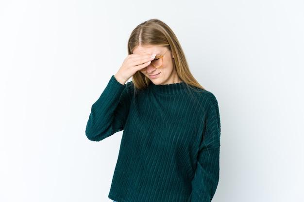 Giovane donna bionda isolata sul muro bianco con mal di testa, toccando la parte anteriore del viso