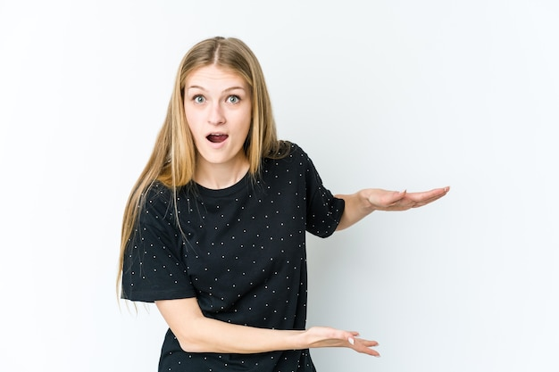 Giovane donna bionda isolata sul muro bianco scioccato e stupito in possesso di uno spazio di copia tra le mani.