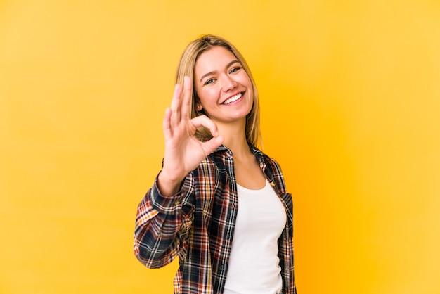 Giovane donna bionda isolata su un muro giallo allegro e fiducioso che mostra gesto giusto