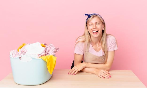 Giovane donna bionda che ride ad alta voce per qualche scherzo esilarante. lavare i vestiti concetto