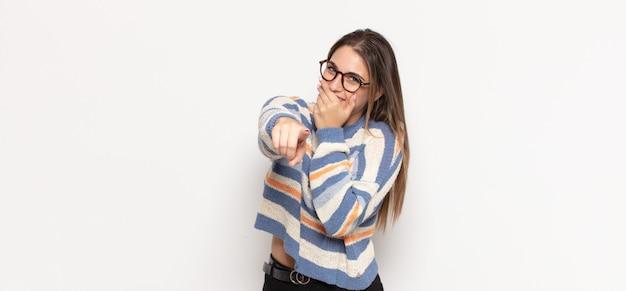 Giovane donna bionda che ride di te, indica la telecamera e ti prende in giro o ti prende in giro