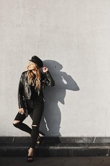 Giovane donna bionda in una giacca di pelle e jeans strappati per godersi il sole all'aperto contro il muro urbano.