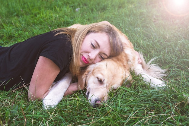 Una giovane donna bionda giace sull'erba con il suo cane. documentalista di razza di cane con una ragazza nel parco.