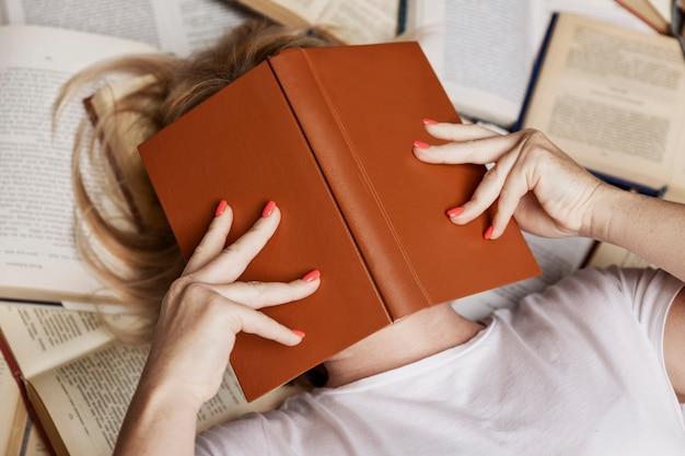 Giovane donna bionda si trova su una pila di libri che copre il viso. istruzione, conoscenza e hobby. avvicinamento.