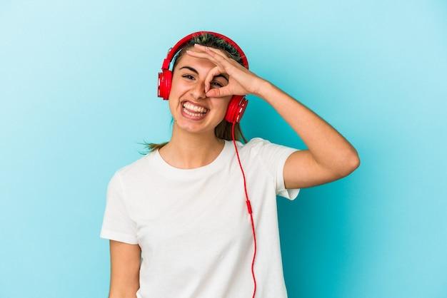 La giovane donna bionda che ascolta la musica sulle cuffie ha eccitato mantenendo il gesto giusto sull'occhio.