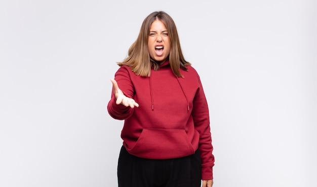 Giovane donna bionda che sembra arrabbiata, infastidita e frustrata che grida wtf