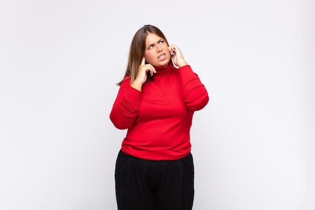 Giovane donna bionda che sembra arrabbiata, stressata e infastidita, coprendo entrambe le orecchie con un rumore assordante, un suono o una musica ad alto volume