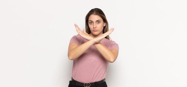 Giovane donna bionda che sembra infastidita e stufo del tuo atteggiamento, dicendo basta! mani incrociate davanti, dicendoti di fermarti