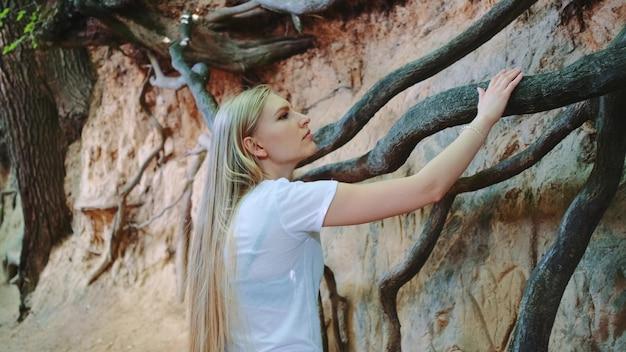 Giovane donna bionda che osserva sulle radici degli alberi esposte nel burrone naturale di loess