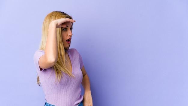 Giovane donna bionda che guarda lontano tenendo la mano sulla fronte